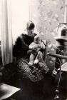 Anna Koehler mit dem Baby Anneliese neben dem alten Holzofen